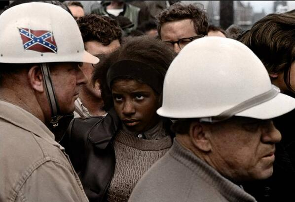 black woman stares down man with confederate flag