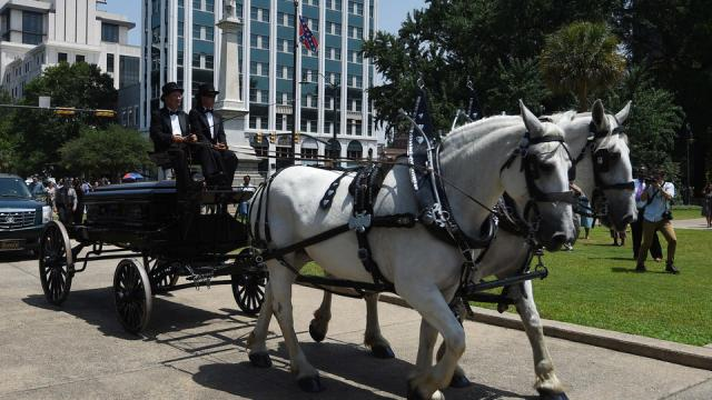 Sen. Clementa Pinckney's body arrives by horse drawn carriage at the South Carolina Statehouse, Wednesday, June 24, 2015, in Columbia, S.C. Pinckney's open coffin was being put on display under the dome where he served the state for nearly 20 years. Pinckney was one of those killed in a mass shooting at the Emanuel AME Church in Charleston. (AP Photo/Rainier Ehrhardt)