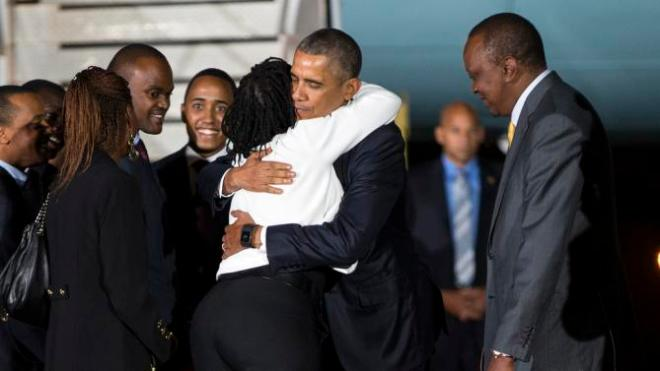 Kenyan President Uhuru Kenyatta, right, watches as President Barack Obama, center, hugs his half-sister, Auma Obama, after he arrived at Kenyatta International Airport, on Friday, July 24, 2015, in Nairobi, Kenya. Obama is traveling on a two-nation African tour where he will become the the first sitting U.S. president to visit Kenya and Ethiopia. (AP Photo/Evan Vucci)