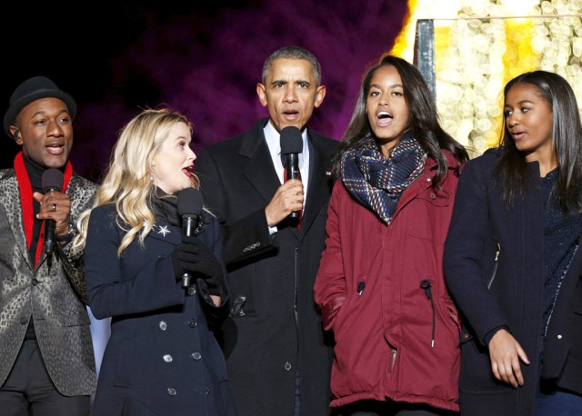 U.S. President Barack Obama sings carols along with (L-R) singer Aloe Blacc, actress Reese Witherspoon and his daughters Malia and Sasha during the National Christmas Tree Lighting and Pageant of Peace ceremony on the Ellipse in Washington December 3, 2015. REUTERS/Kevin Lamarque - RTX1X3JT
