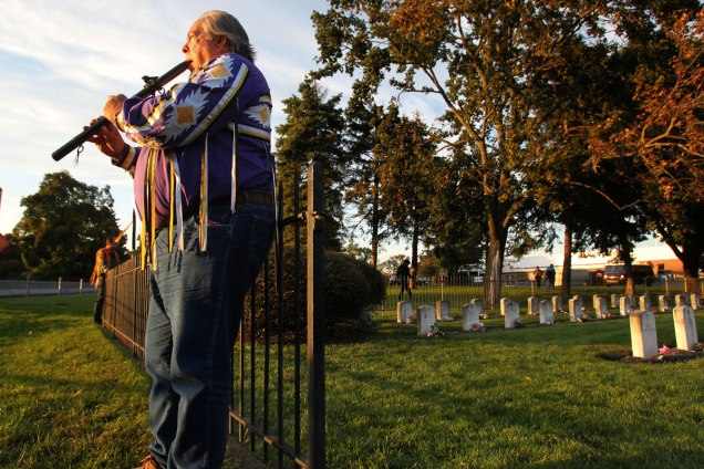 """Warren Petoskey plays his flute at the entrance to the Indian Cemetery at the Carlisle Barracks on Oct. 6, 2012. He had just finished a pipe ceremony to bring peace and healing to himself and his family. Warren's grandfather and great aunt had attended Carlisle. Oct. 6 also marched the anniversary of the first group of students arriving at the Carlisle Indian Industrial School. The Rosebud Sioux in South Dakota have begun efforts to repatriate the remains of the 10 Rosebud students buried on the Carlisle school grounds. Warren had been at the Carlisle Symposium, """"Carlisle, PA: Site of Indigenous Histories, Memories, and Reclamations,"""" held at Dickinson College. CHARLES FOX / Staff Photographer"""