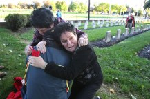 """In sorrow and support, Dr. Kay McGowan, left, a cultural anthropologist at Eastern Michigan University, and Fay Givens, right, Executive Director of the American Indian Services, fall to their knees as they embrace an Randy LeBar in the Indian Cemetery at the Carlisle Barracks on Oct. 6, 2012. They were overcome with emotion upon entering the cemetery for the first time. Kay and Fay are twins of Choctaw and Cherokee descent. Their great grandmother attended the Carlisle Indian School. Randy LeBar is from the band of Blackoot people in northern Ohio. Oct. 6 also marked the anniversary of the first group of students arriving at the Carlisle Indian Industrial School. They were in Carlisle for a symposium at Dickinson College on the Indian school, """"Carlisle, PA: Site of Indigenous Histories, Memories, and Reclamations."""" The Rosebud Sioux in South Dakota have begun efforts to repatriate the remains of the 10 Rosebud students buried on the Carlisle school grounds. CHARLES FOX / Staff Photographer"""