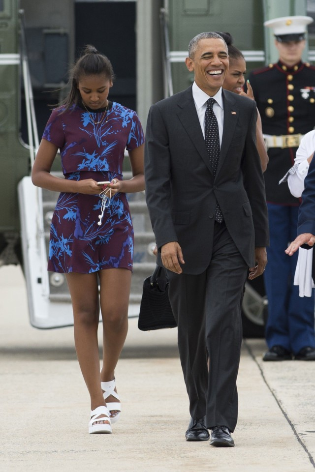 US President Barack Obama, First Lady Michelle Obama and daughter Sasha walk to board Air Force One prior to departing from Andrews Air Force Base in Maryland, August 7, 2015. The Obamas are traveling to Martha's Vineyard, Massachusetts, for a 2-week vacation. AFP PHOTO / SAUL LOEB        (Photo credit should read SAUL LOEB/AFP/Getty Images)