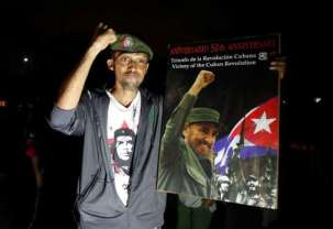 A man reacts while holding a picture of Fidel, as part of a tribute, following the announcement of the death of Cuban revolutionary leader Fidel Castro, in Tegucigalpa