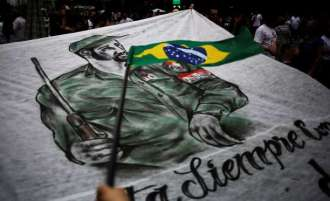 A woman holds a Brazilian flag beside a painting of Cuba's former President Fidel Castro during a protest against a constitutional amendment, known as PEC 55, that limits public spending, in Sao Paulo