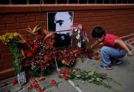 A boy places flowers beside a picture of the late Fidel Castro, as part a tribute outside the Cuban Embassy in Guatemala City