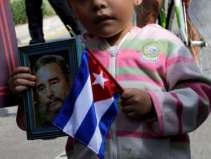A girl holds a picture of Fidel Castro and a Cuban flag during a tribute ceremony, following the announcement of the death of Cuban revolutionary leader Castro outside the Cuban Embassy in Mexico City