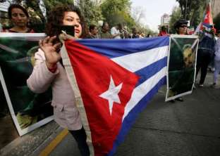 Supporters of Fidel Castro hold Cuban flags and pictures of Castro as they attend a tribute ceremony outside the Cuban Embassy in Mexico City