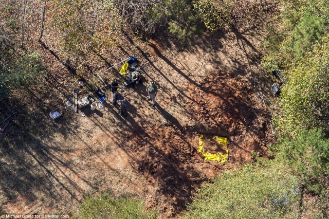 todd-kohlhepp-police-are-seen-standing-around-a-hole-in-the-ground-that-had-been-dug-as-part-of-the-search-for-bodies-on-the-property-on-friday