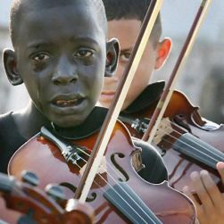 Diego is crying at the funeral of his mentor and teacher, Evandro João da Silva, who was killed in an assault in October of 2009 in Rio De Janerio. Diego's teacher had helped him escape poverty and violence through his kindness and their shared love of music. Diego died in March of 2010 from complications of leukemia.