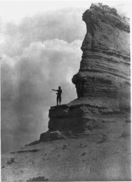 The offering- San Ildefonso Barechested Tewa man, standing high on a cliff, arms stretched before him as he sprinkles cornmeal as an offering at the start of a day, to the sun, or some other deity, or to mundane daily events. Edward S. Curtis Collection