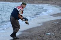A Turkish police officer gently carries the body of three-year-old Aylan Kurdi after he washed ashore Wednesday. He was on a boat of Syrian refugees that sank trying to reach a Greek island.