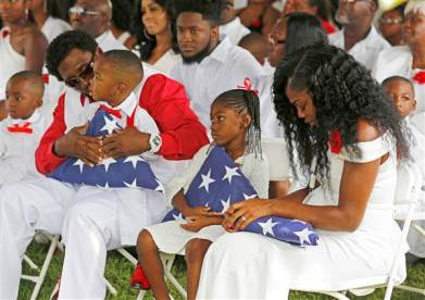 Myeshia Johnson, widow of U.S. Army Sergeant La David Johnson,weeps while holding folded flag presented to her.