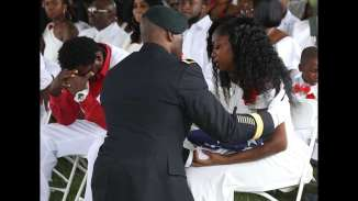 Myeshia Johnson is presented with a folded American flag by a military honor guard member during the burial service for her husband U.S. Army Sgt. La David Johnson at the Memorial Gardens East cemetery on October 21, 2017 in Hollywood, Florida. Sgt. Johnson and three other American soldiers were killed in an ambush in Niger on Oct. 4. (Photo by Joe Raedle/Getty Images)
