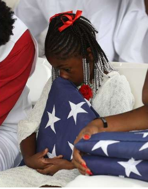 Ah'Leesya Johnson holds a folded American flag given to her during the burial service for her father U.S. Army Sgt. La David Johnson at the Memorial Gardens East cemetery on October 21, 2017 in Hollywood, Florida. Sgt. Johnson and three other American soldiers were killed in an ambush in Niger on Oct. 4.