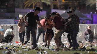 People carry a person at the Route 91 Harvest country music festival after shots were fired David Becker/Getty
