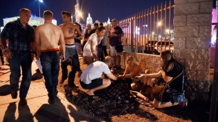 People tend to the wounded outside the Route 91 Harvest Country music festival grounds after a mass shooting Sunday night. At least 50 were killed and hundreds injured in the shooting making it the worst in U.S. history.