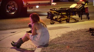 A woman sits on a curb at the scene of a shooting outside of a music festival along the Las Vegas Strip AP/John Locher