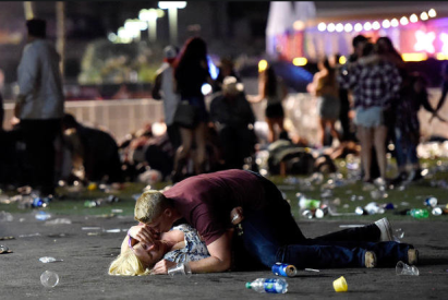 A man lays on top of a woman as others flee the Route 91 Harvest country music festival grounds after a active shooter was reported the night of October 1, 2017 in Las Vegas, Nevada. Police say at least 58 people were killed, plus the gunman, and more than 500 hospitalized, making it the deadliest mass shooting in U.S. history. CREDIT: Getty