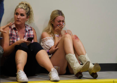 A woman cries while hiding inside the Sands Corporation plane hangar after a mass shooting at the Route 91 Harvest music festival in Las Vegas on Sunday, Oct. 1, 2017. CREDIT: Al Powers/Invision/AP