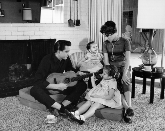 1957 Country Singer Songwriter Johnny Cash Holds A Guitar As His Wife Vivian Liberto And Daughters Rosanne Kathy Look On In