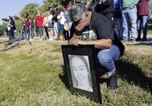 Pat Gibson holds a drawing of Meadow Pollack, a victim of the Marjory Stoneman Douglas High School shooting, as she stands outside of the school as part of a nationwide protest against gun violence, Wednesday, March 14, 2018, in Parkland, Fla. Organizers say nearly 3,000 walkouts are set in the biggest demonstration yet of the student activism that has emerged following the massacre of 17 people at Marjory Stoneman Douglas High School in February. (AP Photo/Lynne Sladky)