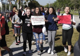 Students from Westglades Middle School walk out of their school as part of a nationwide protest against gun violence, Wednesday, March 14, 2018, in Parkland, Fla. Students across the country participate in walkouts Wednesday to protest gun violence, one month after the deadly shooting inside a high school in Parkland, Fla. (AP Photo/Lynne Sladky)