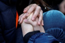 Students from Fiorello H. Laguardia High School hold hands as they sit down on West 62nd street in support of the National School Walkout in the Manhattan borough of New York City, New York, U.S., March 14, 2018. REUTERS/Mike Segar - RC171AC0A9A0